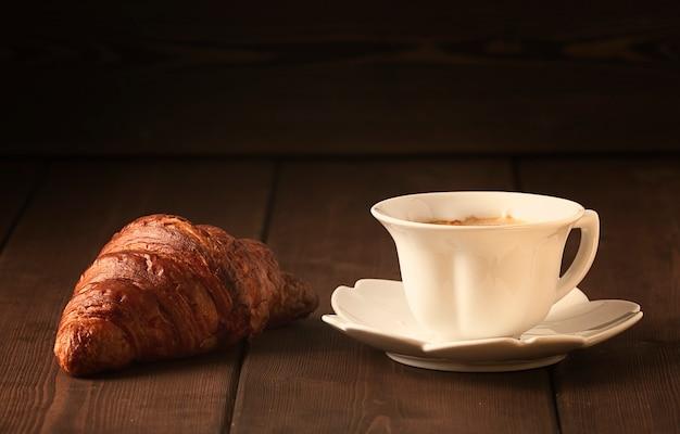 패스트리, 갈색 나무 테이블에 크루아상, 커피 한 잔, 아침 식사, 사람 없음, 소박한 스타일. 고품질 사진