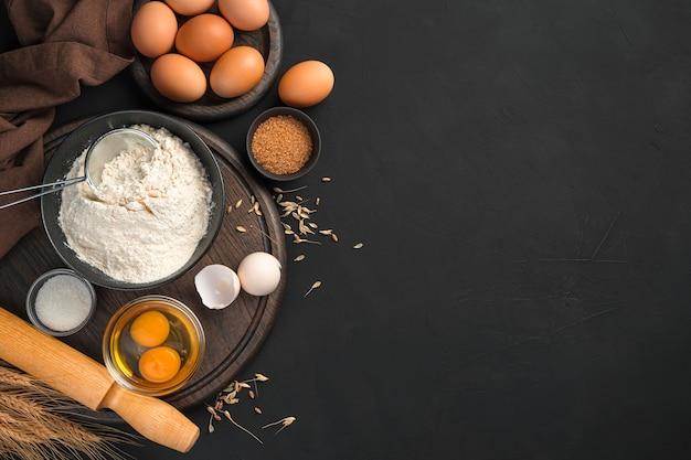 黒の背景に生地の皿を作るためのペストリーの材料小麦粉卵砂糖と麺棒