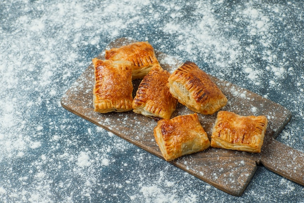 Pastries with sprinkled flour on concrete and cutting board