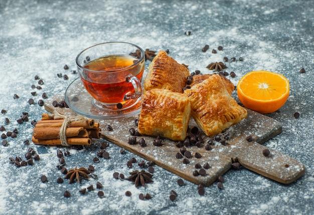 Pasticcini con tè, farina, choco chips, spezie, arancia su cemento e tagliere, veduta dall'alto.