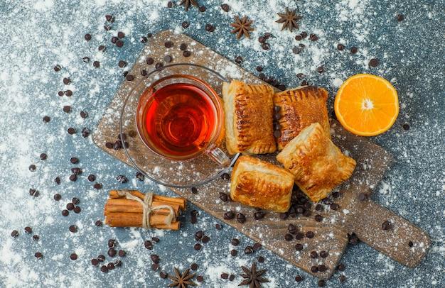 Pasticcini con tè, farina, choco chips, spezie, arancia su cemento e tagliere, vista dall'alto.