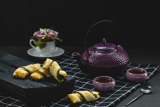 Pastries with tea and flowers on black wooden table, rustic style