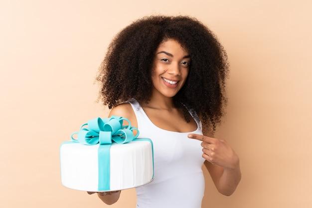 Афро-шеф-кондитер держит большой торт, изолированный на бежевом и указывая на него