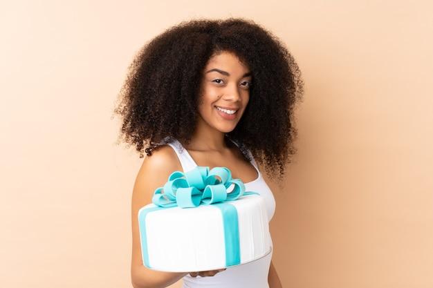 Афро-шеф-кондитер держит большой торт на бежевом и много улыбается
