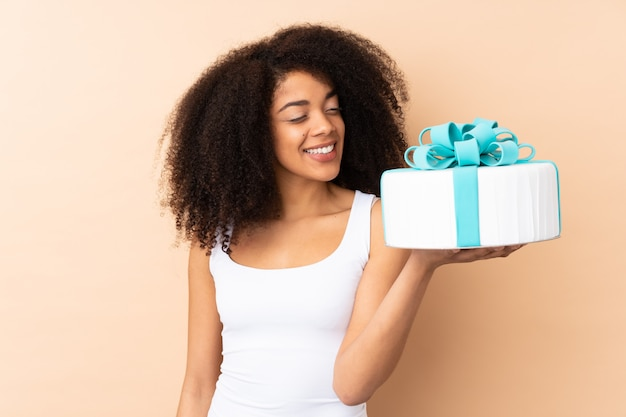 Шеф-кондитер афро-шеф-повар держит большой торт на бежевом с счастливым выражением