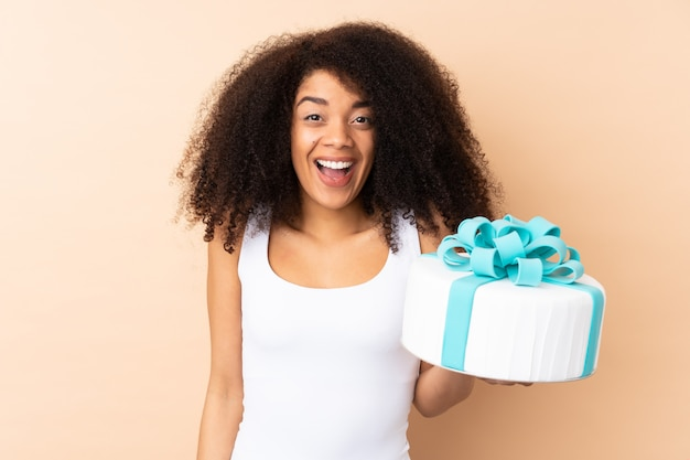Pastry afro chef holding a big cake on beige wall with surprise and shocked facial expression