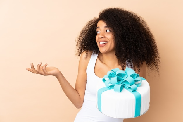 Pastry afro chef holding a big cake isolated on beige with surprise facial expression