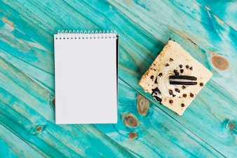 Pastry and spiral notepad on turquoise wooden background