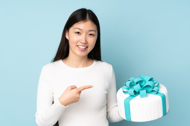 Pastry asian chef holding a big cake on blue wall and pointing it