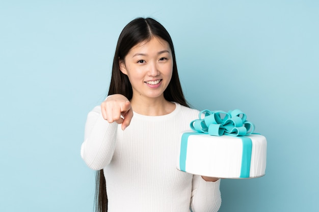 Pastry asian chef holding a big cake on blue wall points finger at you with a confident expression