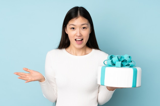 Pastry asian chef holding a big cake on blue wall with shocked facial expression
