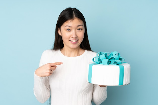Pastry asian chef holding a big cake isolated on blue with surprise facial expression