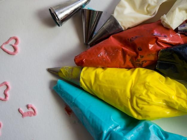 色とりどりのクリームとノズルが付いた絞り袋がテーブルの上にあります