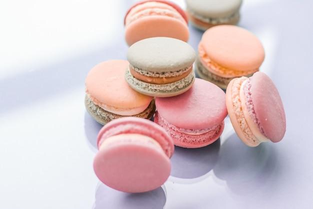 고급 제과 브랜드 휴일 배경 디자인을 위한 파란색 배경의 파리지앵 세련된 카페 디저트 달콤한 음식과 케이크 마카롱에 있는 패스트리 베이커리 및 브랜딩 개념 프랑스 마카롱