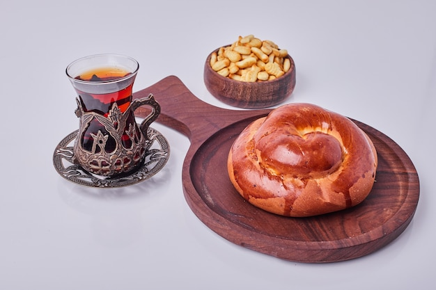 A pastry bun served with fried peanuts and a glass of tea