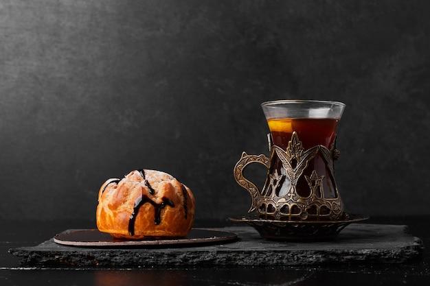 Un panino di pasticceria con un bicchiere di tè.