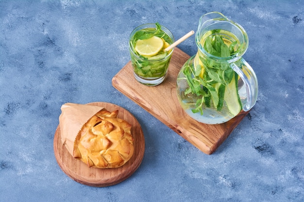 Pastry bun with mojito on a wooden board on blue