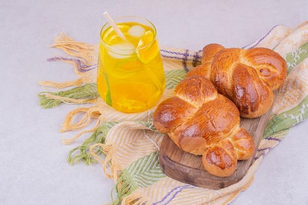 レモネードのガラスと木の板のペストリーパン