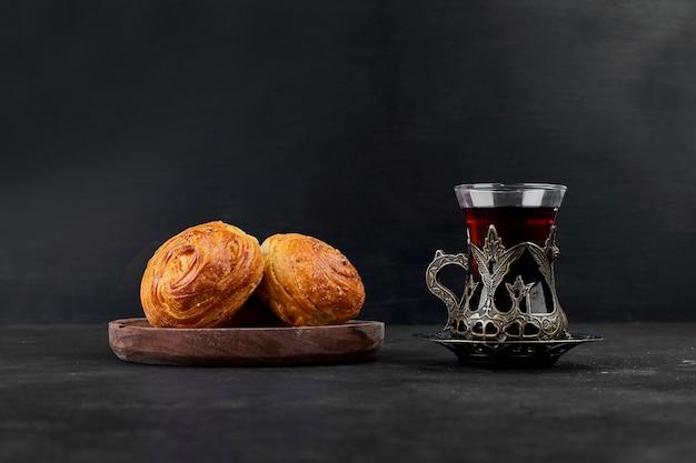 Булочки кондитерские со стаканом чая на черном фоне. фото высокого качества