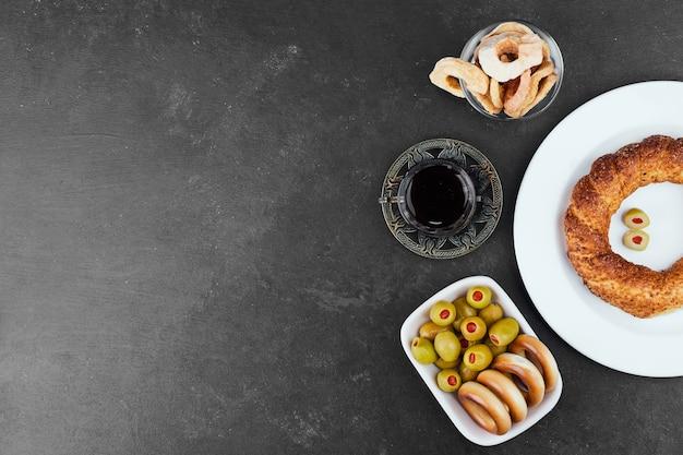Булочки выпечки с стаканом чая с маринованными оливками, вид сверху.