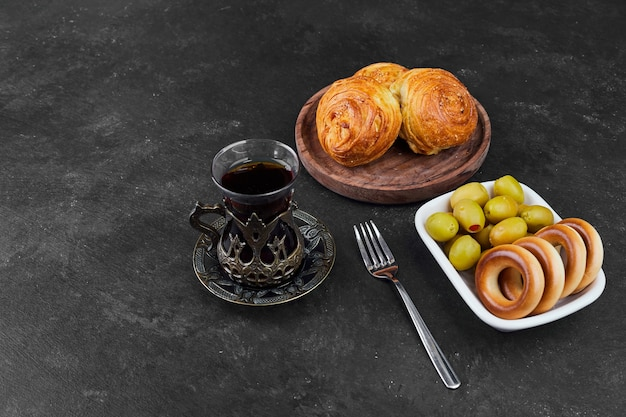 Pastry buns with a glass of tea with marinated olives.