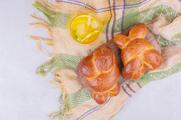 Pastry buns on a wooden board with a glass of lemonade