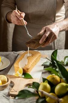 Pasticcere che aggiunge condimento alla torta al limone