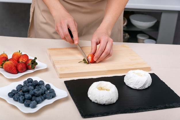 Pastry chef cuts strawberries to make meringue fruit cakes. hands of confectioner.