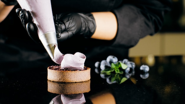 Pastry chef decorates biscuit with purple cream from pastry bag, close-up.