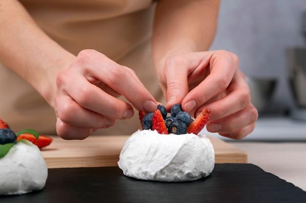 Шеф-кондитер украшает торт свежей клубникой и черникой