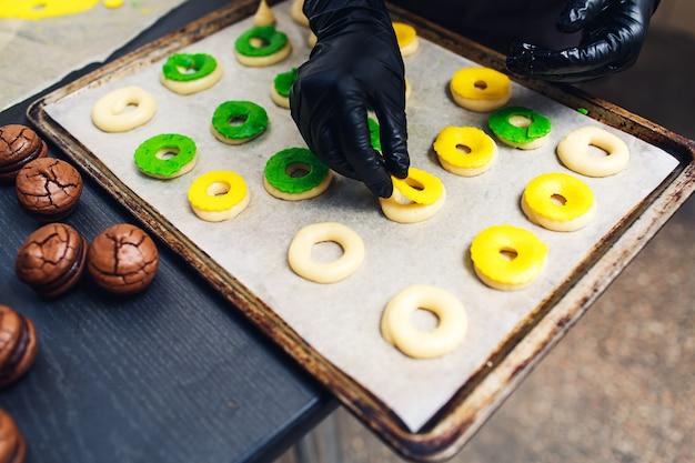 Шеф-кондитер украшает сырые профитроли зеленым и желтым песочным тестом.