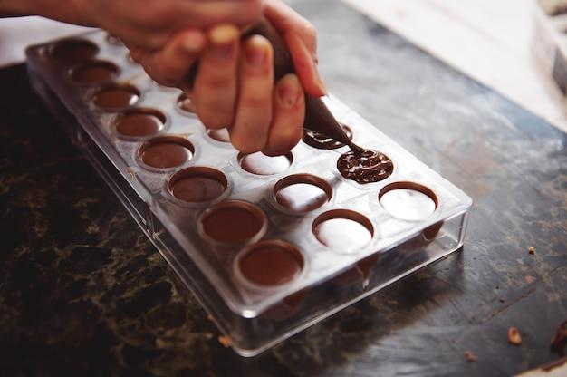 空のチョコレート型に詰め物を詰めたパティシエが、贅沢な手作りチョコレート製品をさらに準備します。閉じる