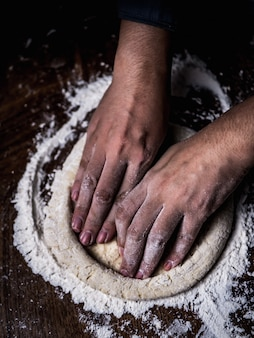 Pastry chef hand kneading raw dough with sprinkling white flour over kitchen table.