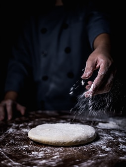 Pastry chef hand sprinkling white flour over raw dough on kitchen table.