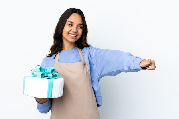 親指を立てるジェスチャーを与える孤立した大きなケーキを保持しているパティシエ