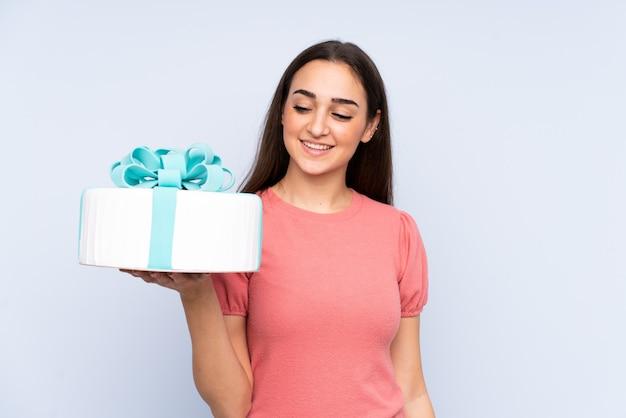 幸せな表情で青い壁に分離された大きなケーキを保持しているパティシエ