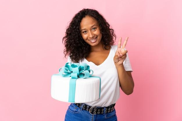 ピンクの笑顔と勝利のサインを示して分離された大きなケーキを保持しているパティシエ