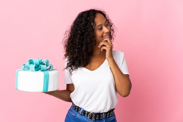 ピンクで隔離の大きなケーキを持っているパティシエは、アイデアを考えて側面を見て