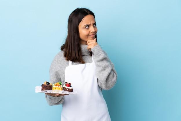 고립 된 큰 케이크를 들고 생 과자 요리사