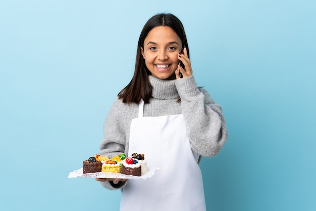 누군가와 휴대 전화로 대화를 유지하는 격리 된 파란색에 큰 케이크를 들고 생 과자 요리사.