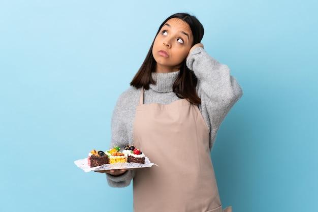 Шеф-кондитер держит большой торт над изолированной синей стеной расстроен и закрывает уши