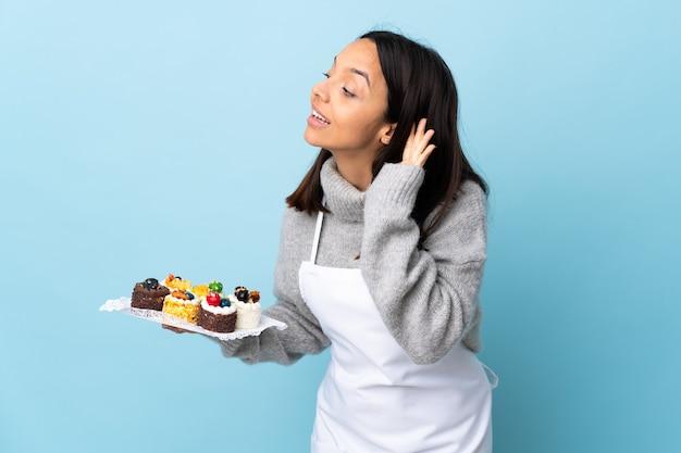귀에 손을 넣어 뭔가를 듣고 고립 된 파란색 벽에 큰 케이크를 들고 생 과자 요리사.