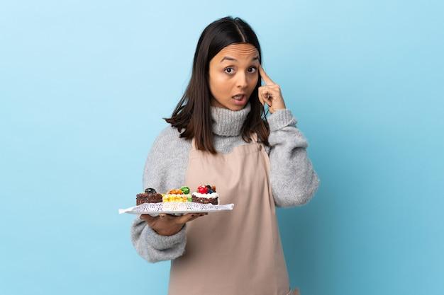 アイデアを考えて孤立した青い壁の上に大きなケーキを保持しているパティシエ。