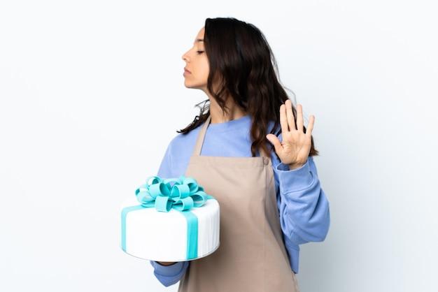Шеф-кондитер держит большой торт над изолированной белой стеной, делая жест стоп и разочарованный