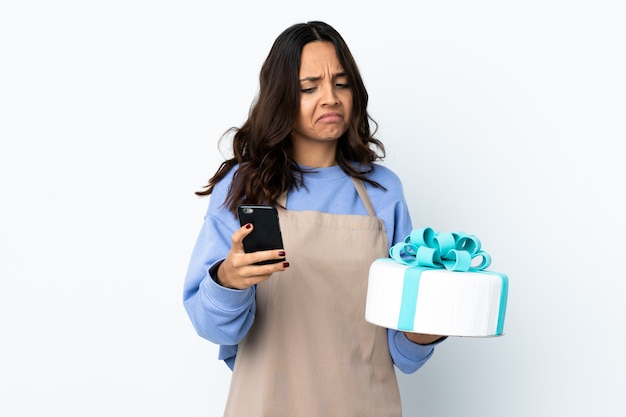 孤立した白い壁に大きなケーキを持って考えてメッセージを送信するパティシエ