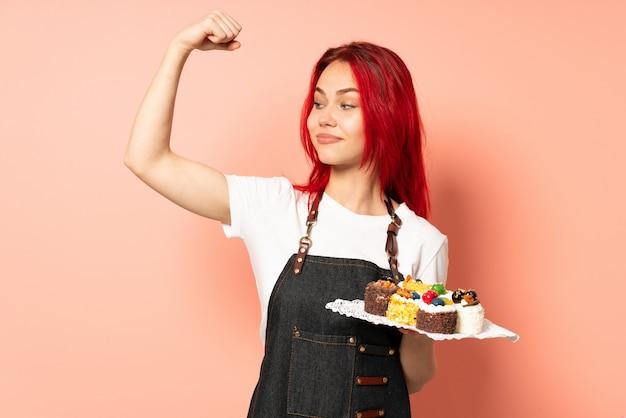 강한 제스처를 하 고 분홍색 배경에 고립 머핀을 들고 생 과자 요리사