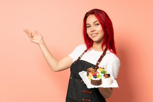와서 초대 측면에 손을 연장 분홍색 배경에 고립 머핀을 들고 생과자 요리사