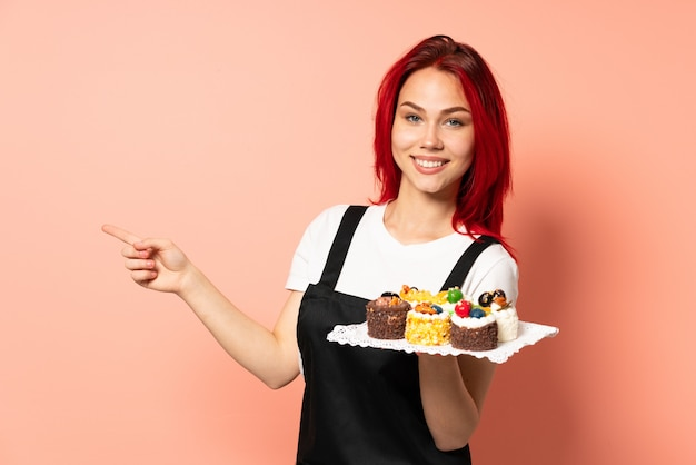 분홍색 배경 쪽을 가리키는 손가락에 고립 된 머핀을 들고 생과자 요리사