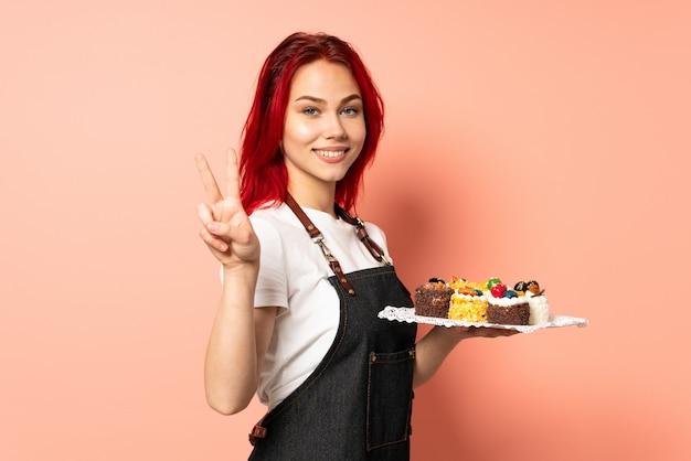 미소하고 승리 기호를 보여주는 분홍색 배경에 고립 머핀을 들고 생과자 요리사