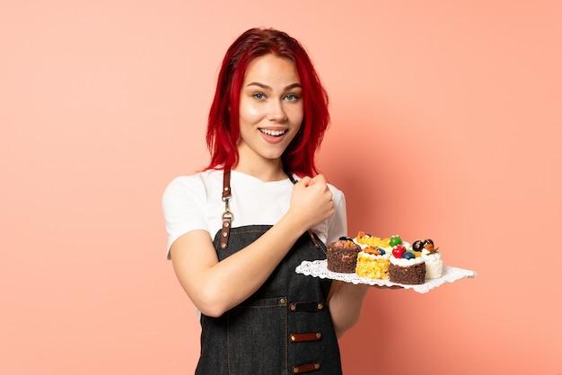 승리를 축하 핑크 벽에 고립 된 머핀을 들고 생과자 요리사